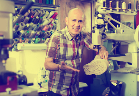 broaching: Elderly man stitching shoes on leather sewing machine at factory Stock Photo