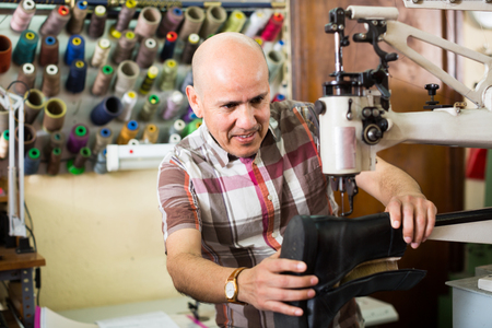 broaching: specialist stitching shoes on leather sewing machine at factory