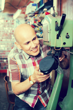 broaching: Smiling mature workman  stitching footwear on machine in shoe atelier Stock Photo