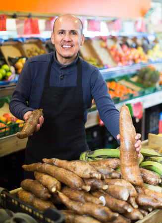 Smiling senior worker selling ripe cassava roots in supermarket Stock Photo