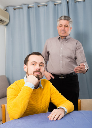 Mature father talking seriously and instructs his son at home