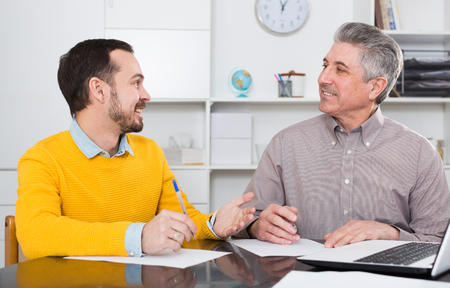 Man and mature bank employee discuss and sign credit agreement in office Stok Fotoğraf