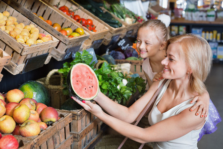 Portrait of smiling positive charming woman and cheerful cute girl buying fresh fruits in grocery shop