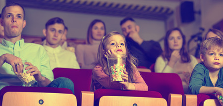 captivated: Number of smiling charming people enjoying film screening and popcorn in cinema