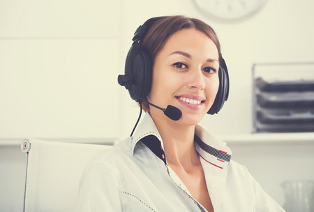 Portret of positive young woman talking with customer using hands-free set at call center Stock Photo