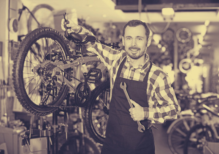 qualitatively: Handsome young man working on master mechanic assembling bicycle equipment