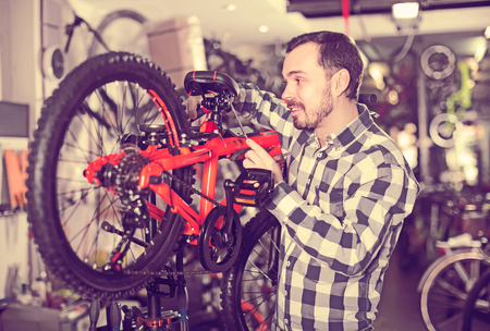 qualitatively: thoughtful male mounts bicycle parts for assembly bike in sports shop Stock Photo