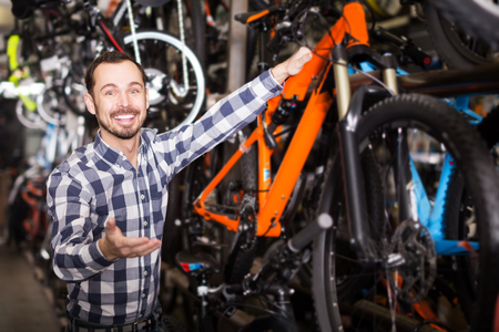 Young man looks at bicycle frame in sports store Stock Photo