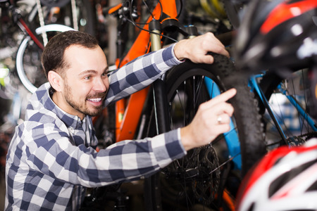 Young smiling man points to interesting details of bicycle in bike shop