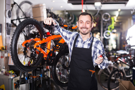 Master is working with bicycles brakes in sports workshop. Stock Photo