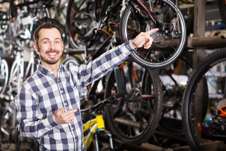 smiling man in sports shop treats bicycles from a range and points up on interesting details