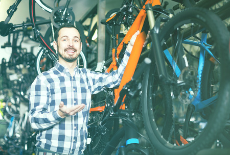 qualitatively: happy spanish  man in sports workshop mounts bike using special tools Stock Photo