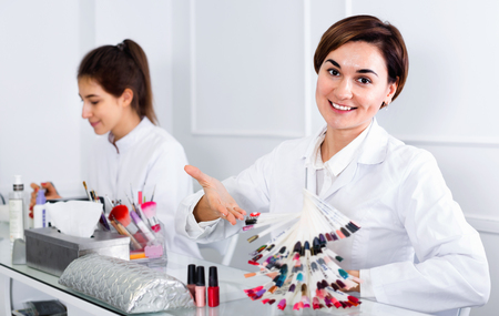 schemes: Pleasant cheerful female manicurist showing lacquer color schemes in nail salon