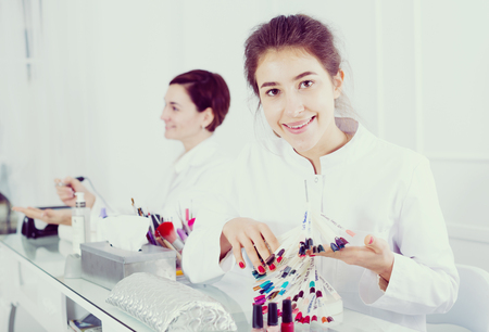 schemes: Smiling female manicurist showing lacquer color schemes in nail salon Stock Photo