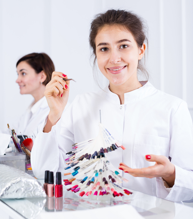 schemes: Pretty woman doing nails displaying polish color schemes in nail salon Stock Photo