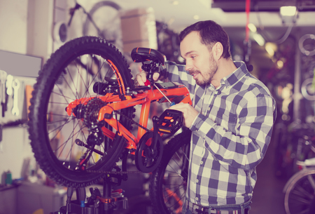 cradling: Young man fastens bicycle seat with a screwdriver in the sports shop