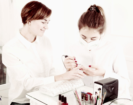 Young female client doing nails in shellac technique in nail salon