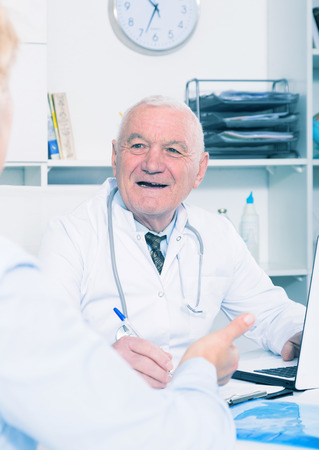 Senior woman having consultation with male doctor in hospital
