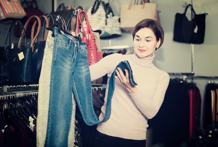 acquiring: Female customer  checks the quality of womens jeans in a clothing store Stock Photo