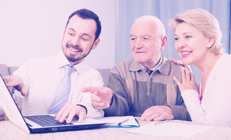 accounts payable: Mature woman and her eldery father studying agreement conditions with smiling manager
