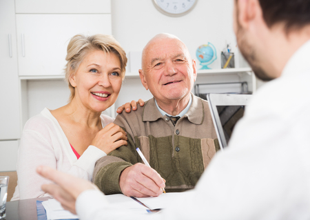 Elderly man and mature woman consulting with employee in social service office