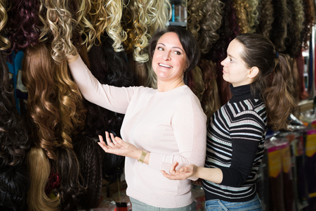 Women choosing clip-in natural hair extension at store