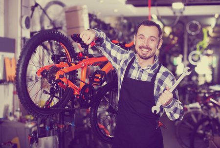 qualitatively: Positive young man working on master mechanic assembling bicycle equipment