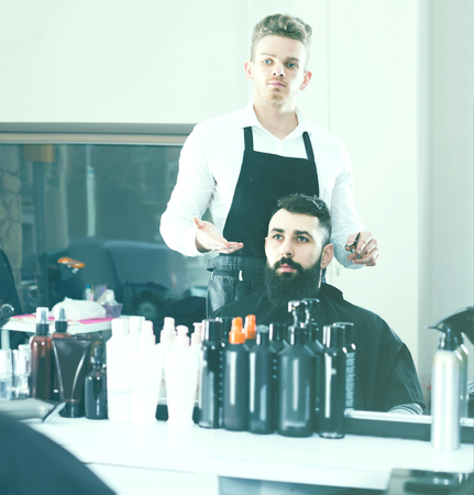 scandalous: Young european client feeling discontent about his new haircut at hair salon