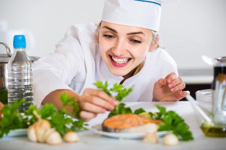 jorobado: Feliz joven cocinero con salmón preparado en la cocina profesional Foto de archivo
