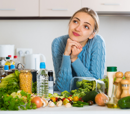Confused girl in sweater thinking what to cook for lunch