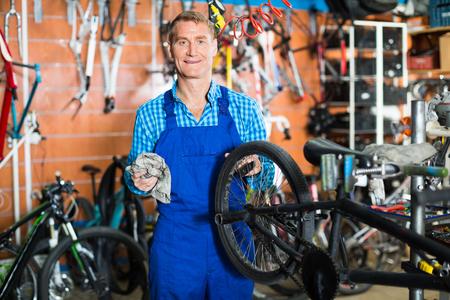 positive smiling man seller wearing uniform fixing bike wheel in store