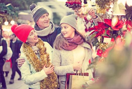 Cheerful family of three choosing Christmas star flower at  Christmas market Stock Photo