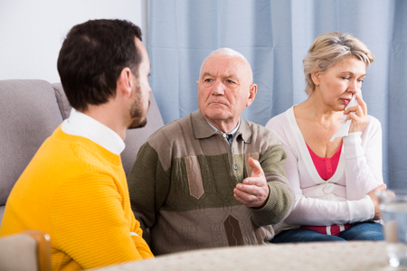 Aged grandfather teaches and instructs his young grandson in front of his mother