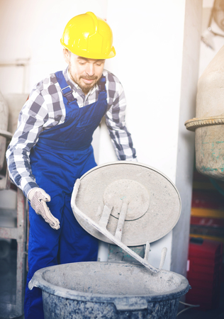 Male worker starting to work with cement mixer at workshop