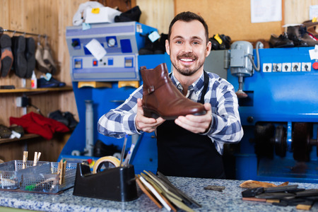 resulted: Young glad friendly  male worker demonstrating repaired shoes in shoe repair workshop