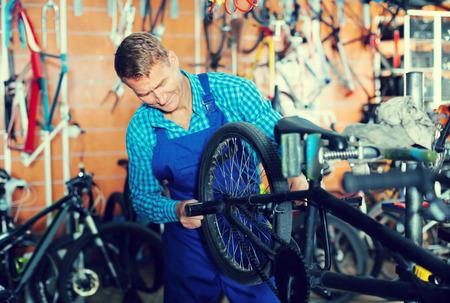 Positive man seller wearing uniform fixing bike in sport store