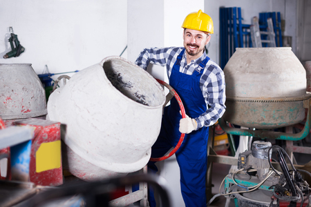 happy russian working man practicing his skills with mixing unit at workshop Stock Photo