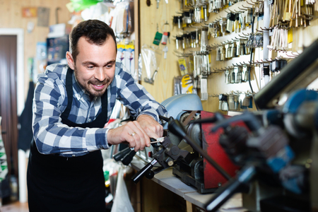 specialized job: Young  friendly smiling male worker using his tools for repairing in specialized workshop
