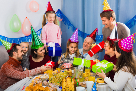 familia animada: Large cheerful positive  family presenting gifts to girl during birthday party