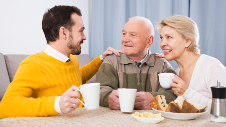 kin: Smiling grandfather, mature mother and son together having breakfast at table at home