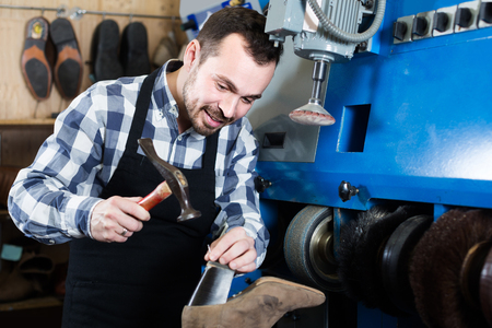 specialized job: positive english male worker fixing failed shoes in shoe repair workshop