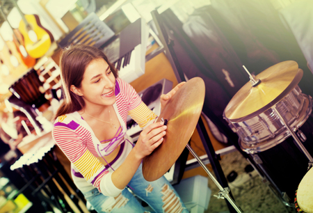 Happy smiling teenage girl shopping drum kit in music instruments studio