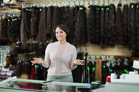 Shop friendly pleasant woman posing at counter with artificial and natural hair