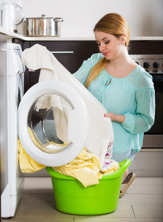 Tired woman with musty linen after lame laundry at home Stock Photo