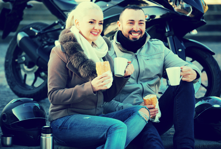 Portrait of young couple drinking coffee and chatting near motorcycle Stock Photo