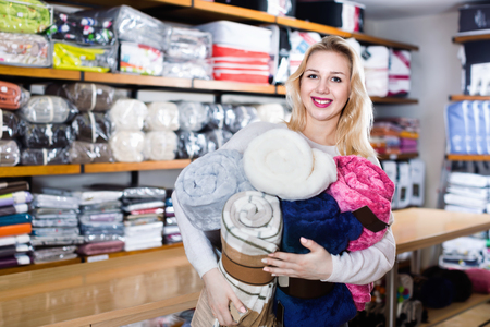 boasting: Young  positive female customer boasting purchased home textiles in textile shop