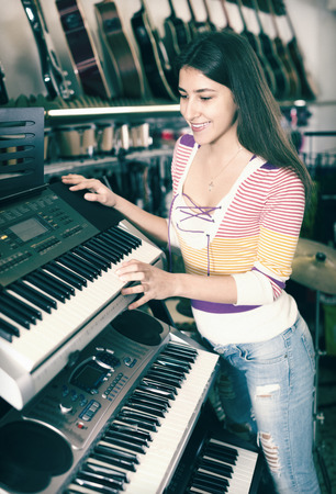 Smiling girl selecting control keyboard for synthesiser in shop