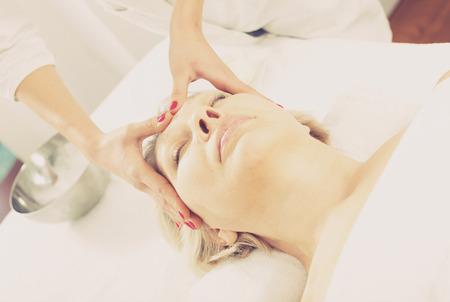 Anciana mujer sonriente con masaje facial profesional en el salón de spa