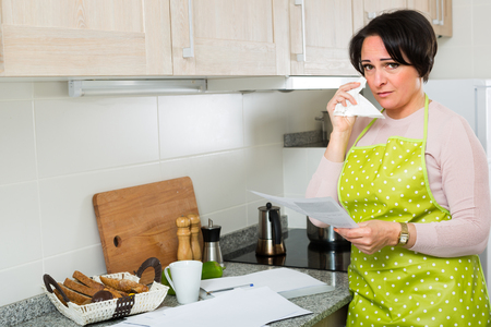 householder: Sad brunette woman looking through financial documents and crying at home kitchen Stock Photo