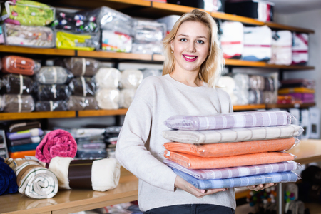 boasting: Young  cheerful positive female customer boasting purchased home textiles in textile shop Stock Photo